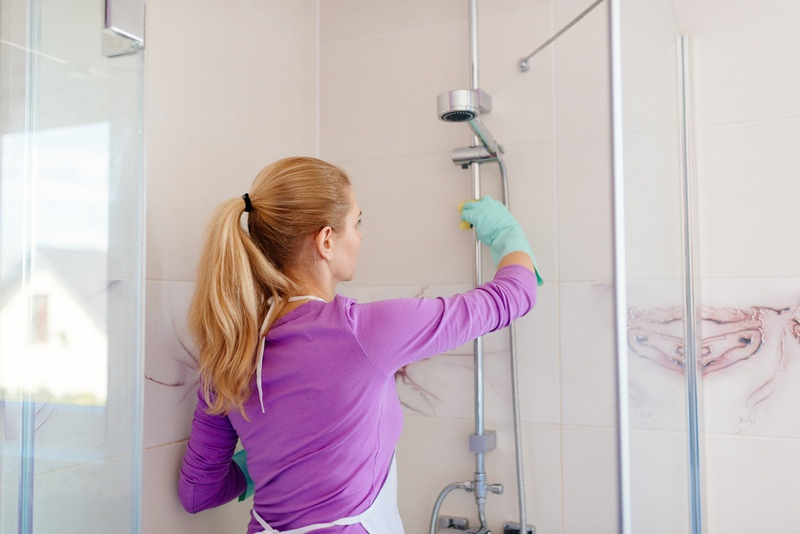 Young woman in white apron cleaning shower