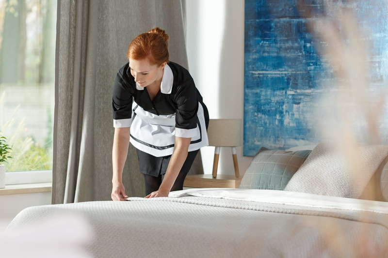 Chambermaid cleaning bedding