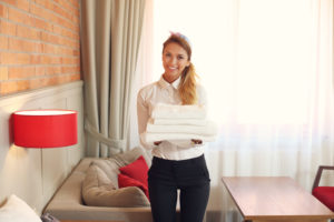 Maid with fresh towels in hotel room