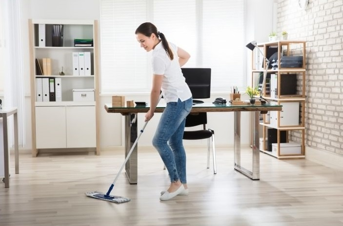 Maid cleaning the house floor with a mop