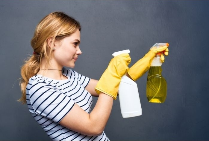 Professional Female maid cleaning wall