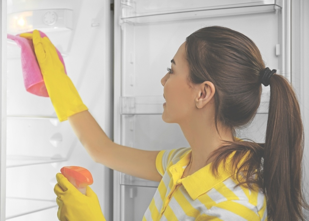 girl deep cleaning fridge